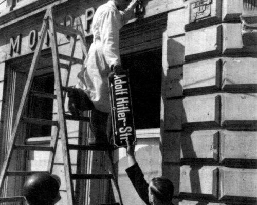 Adolf-Hitler-Straßenschild wird abmontiert, 1945